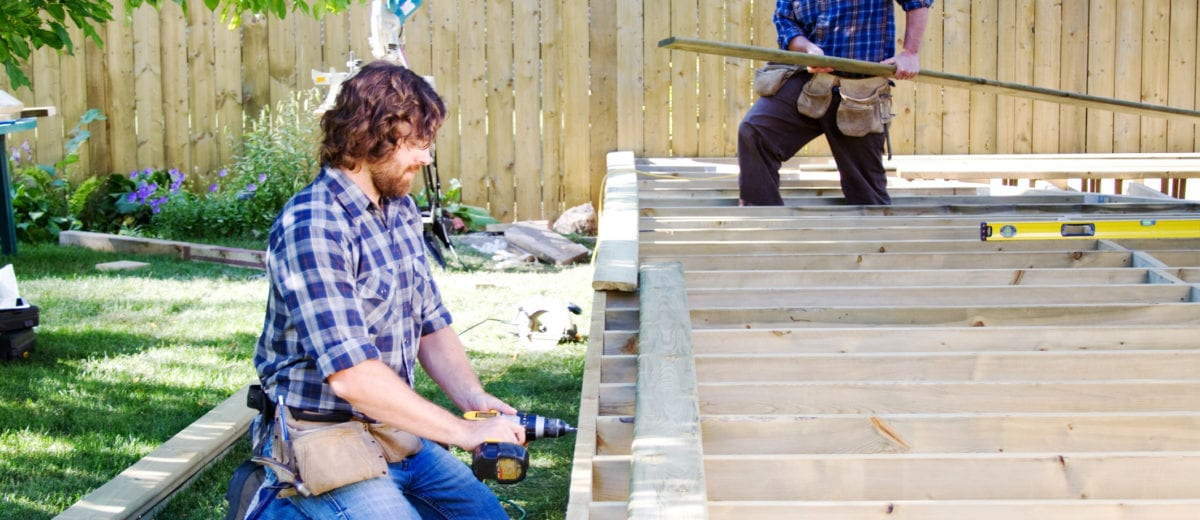 photo of men working on a deck in the summer