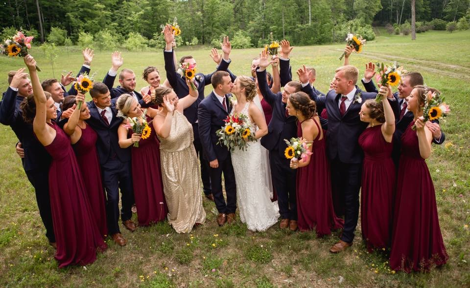 photo of bride and groom kissing while bridal party celebrates