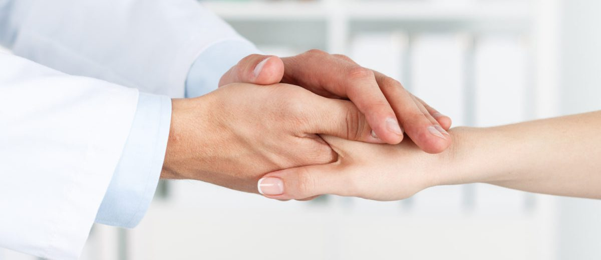 Friendly male doctor's hands holding female patient's hand for encouragement and empathy.