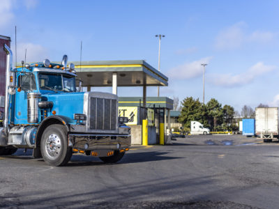 Shiny blue classic American bonnet day cab big rig semi truck with lot of chrome accessories with dry van semi trailer for transportation commercial cargo moving on truck stop with fuel station