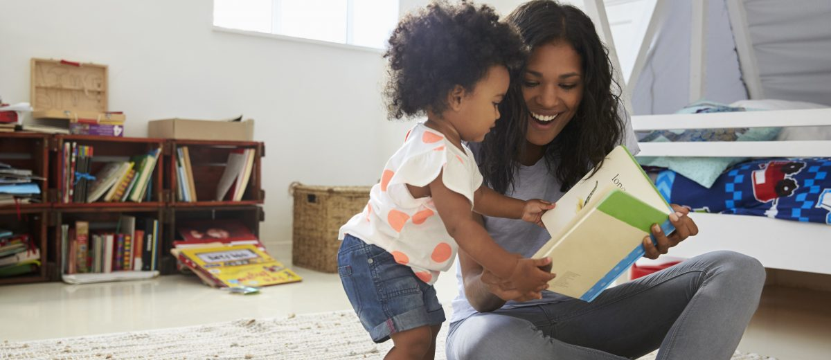 Mother And Baby Daughter Reading Book In Playroom Together