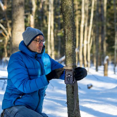 alessio mortelliti setting up trail cam on a tree outside in the snow