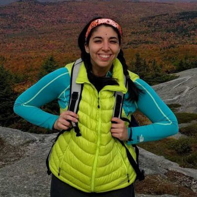 Stephanie in lime green vest with fall foliage in background