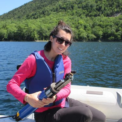 Rachel Fowler holding a water quality sensor on a boat with water and mountain in background